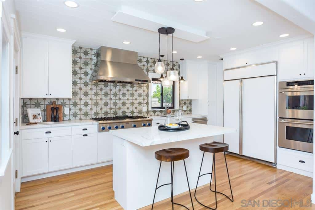 This charming kitchen has two simple wrought iron stools with dark wooden seats. They stand out against the stark white kitchen island with a white countertop. This is mirrored by the peninsula that is augmented by the green patterned backsplash.