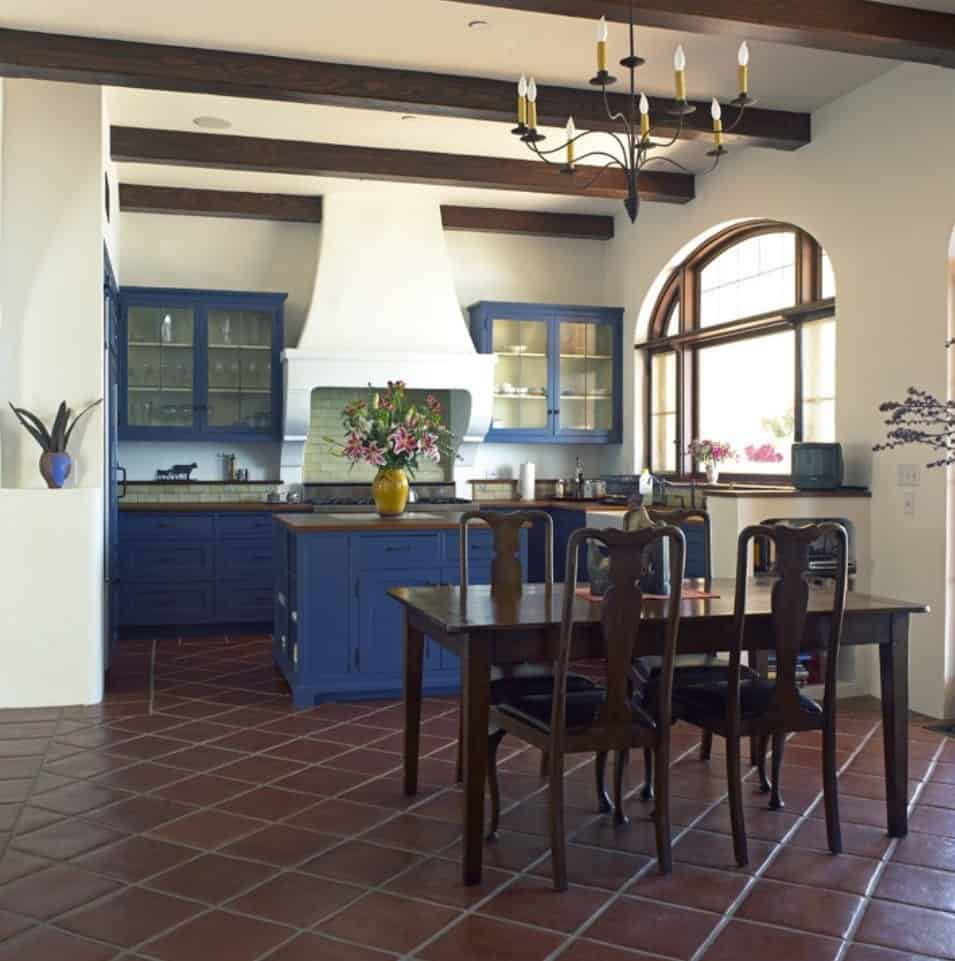 The brilliant blue shaker cabinets and drawers stand out against the white walls and the dark terracotta flooring tiles. This matches with the exposed wooden beams of the white ceiling and the wooden chairs and table of the informal dining area.