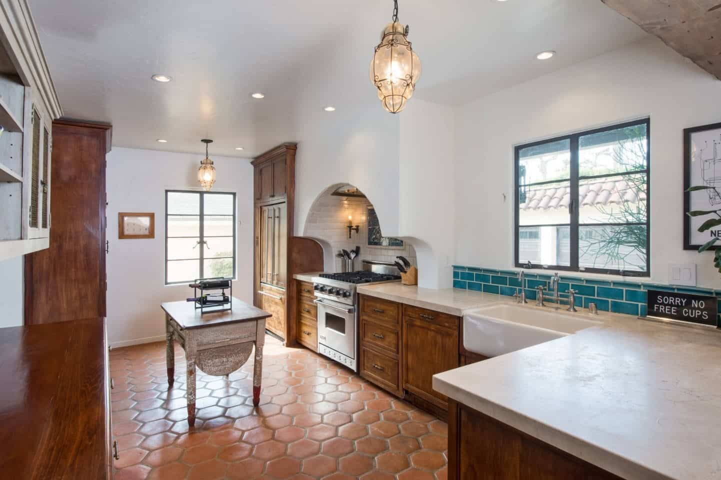 The hexagonal terracotta flooring tiles provide a complex earthy background for the wooden L-shaped kitchen peninsula with white countertops that blend with the arch of the cooking area and is contrasted by the green backsplash.