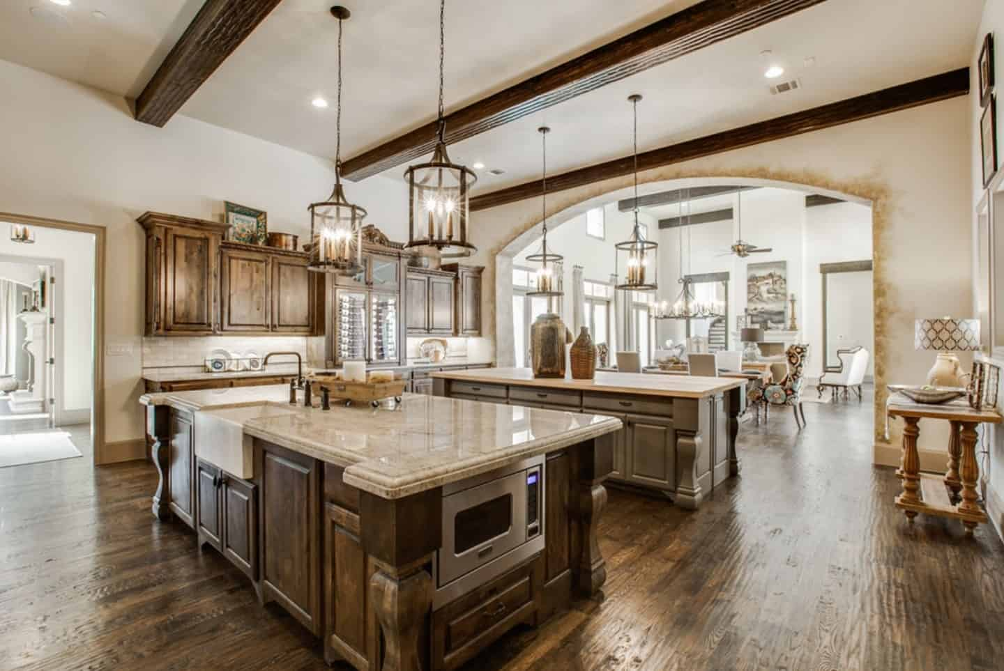 The hardwood flooring has a textured finish to it that works well with the pair of wooden kitchen islands with the same tone. They both have beige marble countertops and topped with lantern-like pendant lights from the white ceiling with exposed wooden beams.
