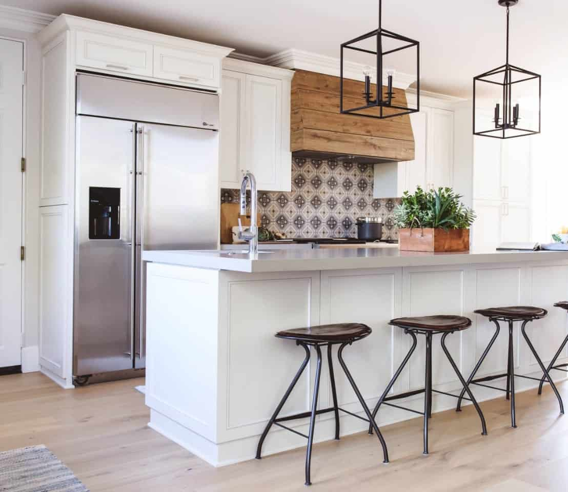 The light hardwood flooring is a nice complement to the white shaker cabinets and drawers of the kitchen island topped with wrought iron pendant lights and peninsula with green patterned tiles for its backsplash at the cooking area.