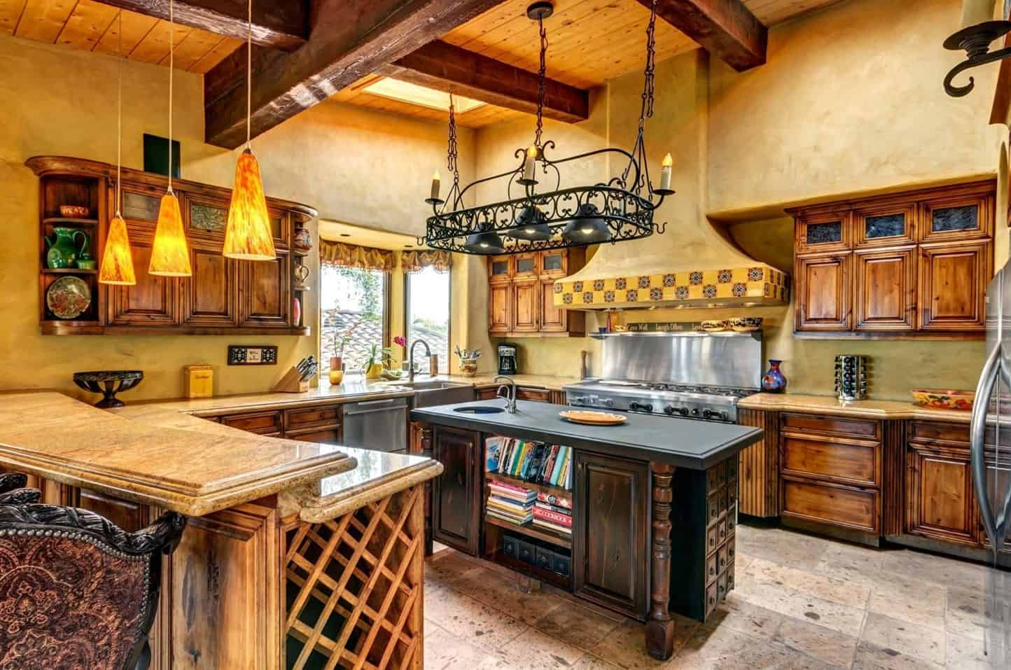 From the wooden ceiling hangs an intricate dark wrought iron structure that supports pendant lights. This matched with the matte dark countertop of the wooden kitchen island surrounded by a large U-shaped wooden peninsula.