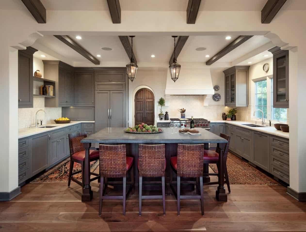 The light gray shaker cabinets and drawers of this Spanish-style kitchen works well with the hardwood flooring and the white tray ceiling that has exposed dark wooden beams that matches with the kitchen island and its stools.