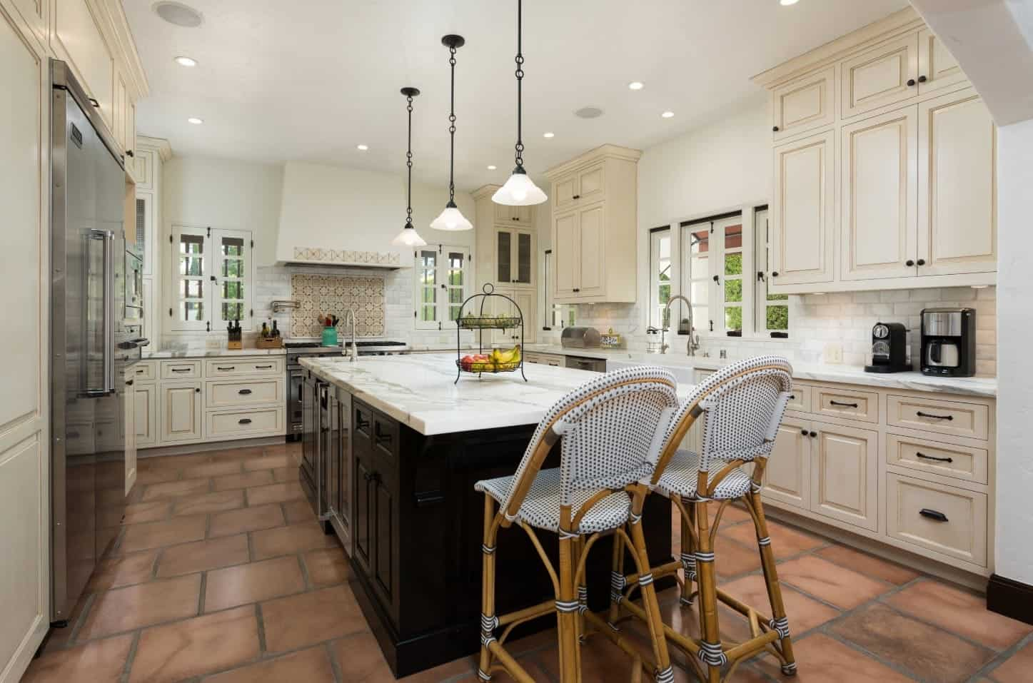 The off-white hue of the shaker cabinets and drawers of the L-shaped peninsula complements the white walls and white ceiling. This ceiling hangs pendant lights over the white marble countertop of the dark wooden kitchen island that stands out against the terracotta flooring tiles.