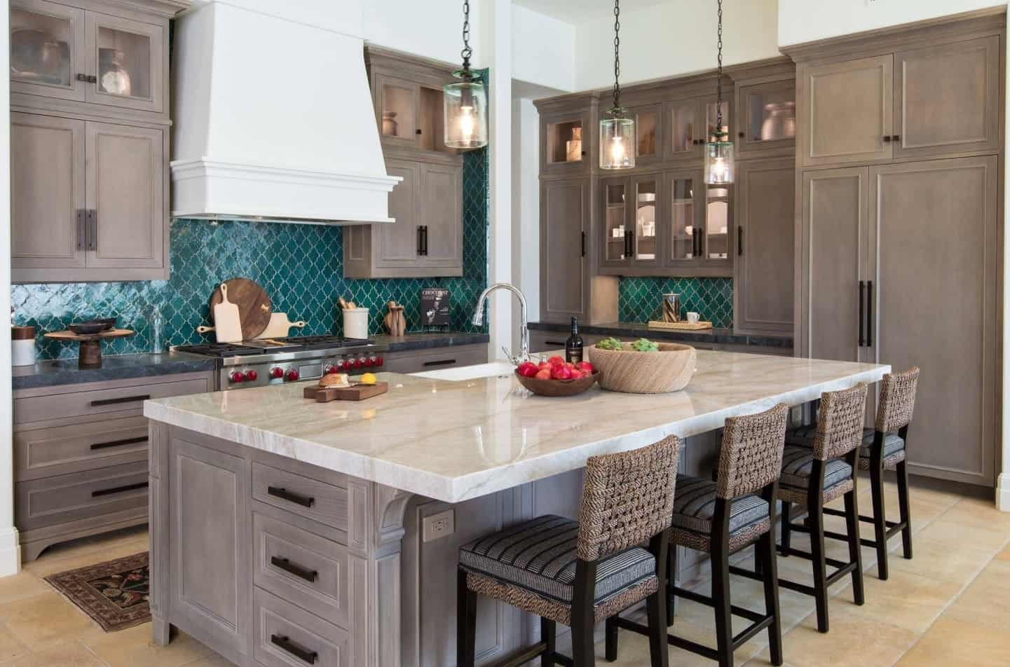 The bright green tiles of the backsplash stands out in this Spanish-style kitchen filled with gray shaker cabinets and drawers with matching black handles matching the wooden legs of the rustic stools with woven wicker backs.