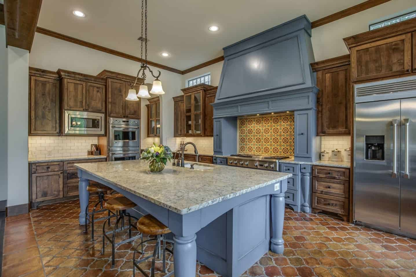The delightful light blue palette of the wooden kitchen island has a stand out quality to it against the terracotta flooring and the white marble countertop. This setup is mirrored by the cooking area that has the same hue to the wooden structure housing the stove-top oven.