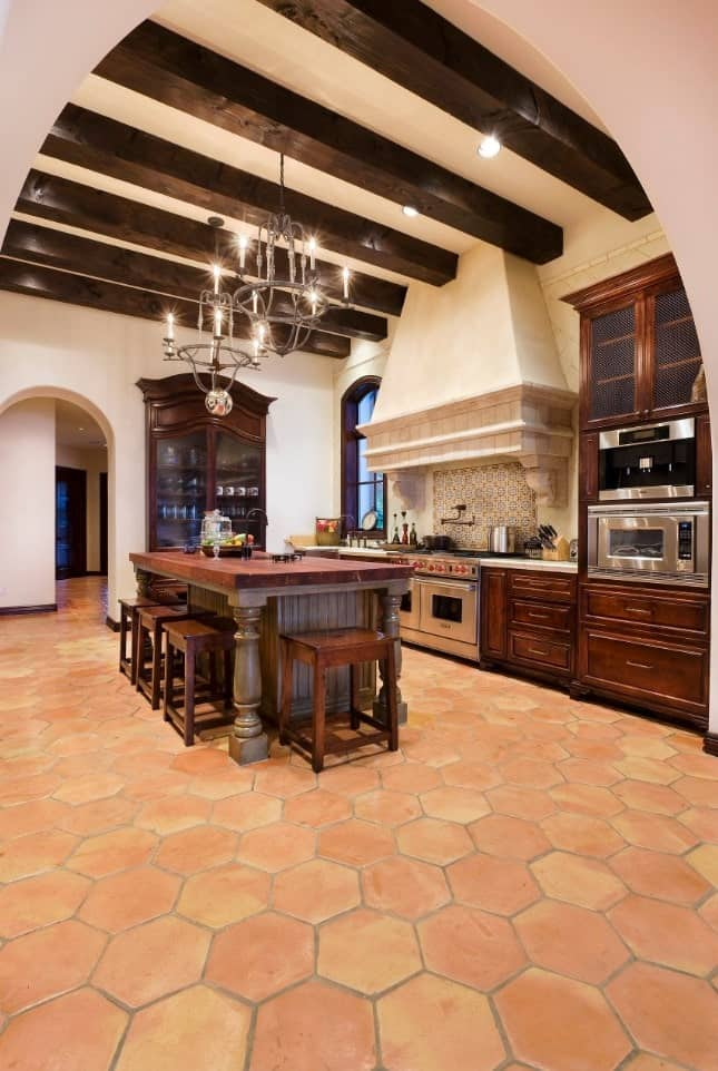 The large vent hood over the stove-top oven blends with the walls and ceiling that has several exposed wooden beams that support a couple of brilliant chandeliers that complements the terracotta flooring tiles with warm yellow lights.