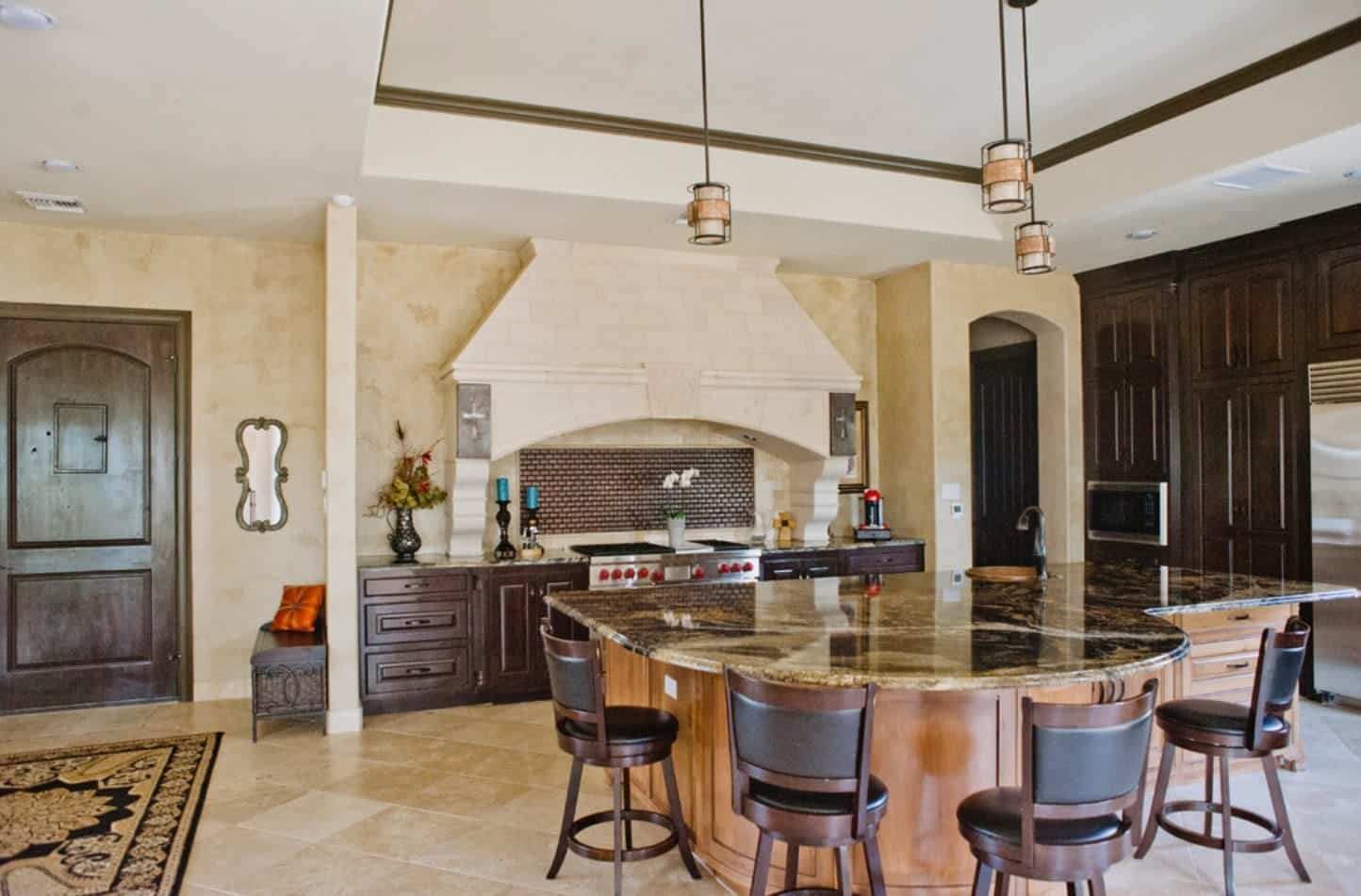 The white tray ceiling of this spacious and bright kitchen bears three charming pendant lights over the large brown marble countertop of the kitchen island large enough for an attached informal dining area with wooden stools that have black leather seats and cushions.