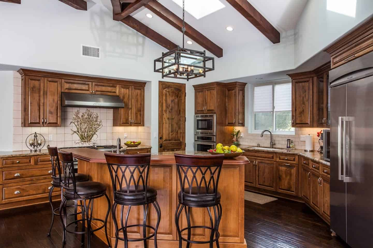 The black wrought iron stools with matching black leather seat cushions stand out against the wooden kitchen and matches with the lantern-like pendant light. This hangs from a shed ceiling with exposed wooden beams that match the hardwood flooring.
