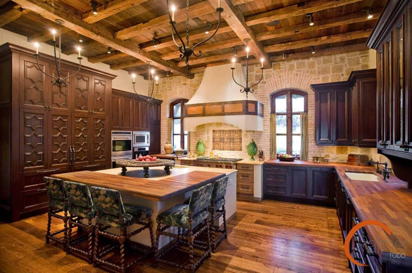 The wooden ceiling has exposed wooden beams crisscrossing each other and also supports the simple wrought iron chandeliers that cast warm yellow lights complementing the dark wooden cabinets and drawers of the L-shaped peninsula.