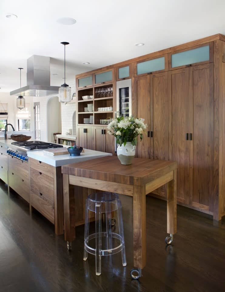 The wooden cabinetry of the peninsula matches with the wooden kitchen island with an attached table at its end with wheels and paired with a modern plastic stool. These stand out against the dark hardwood flooring and the white ceiling.