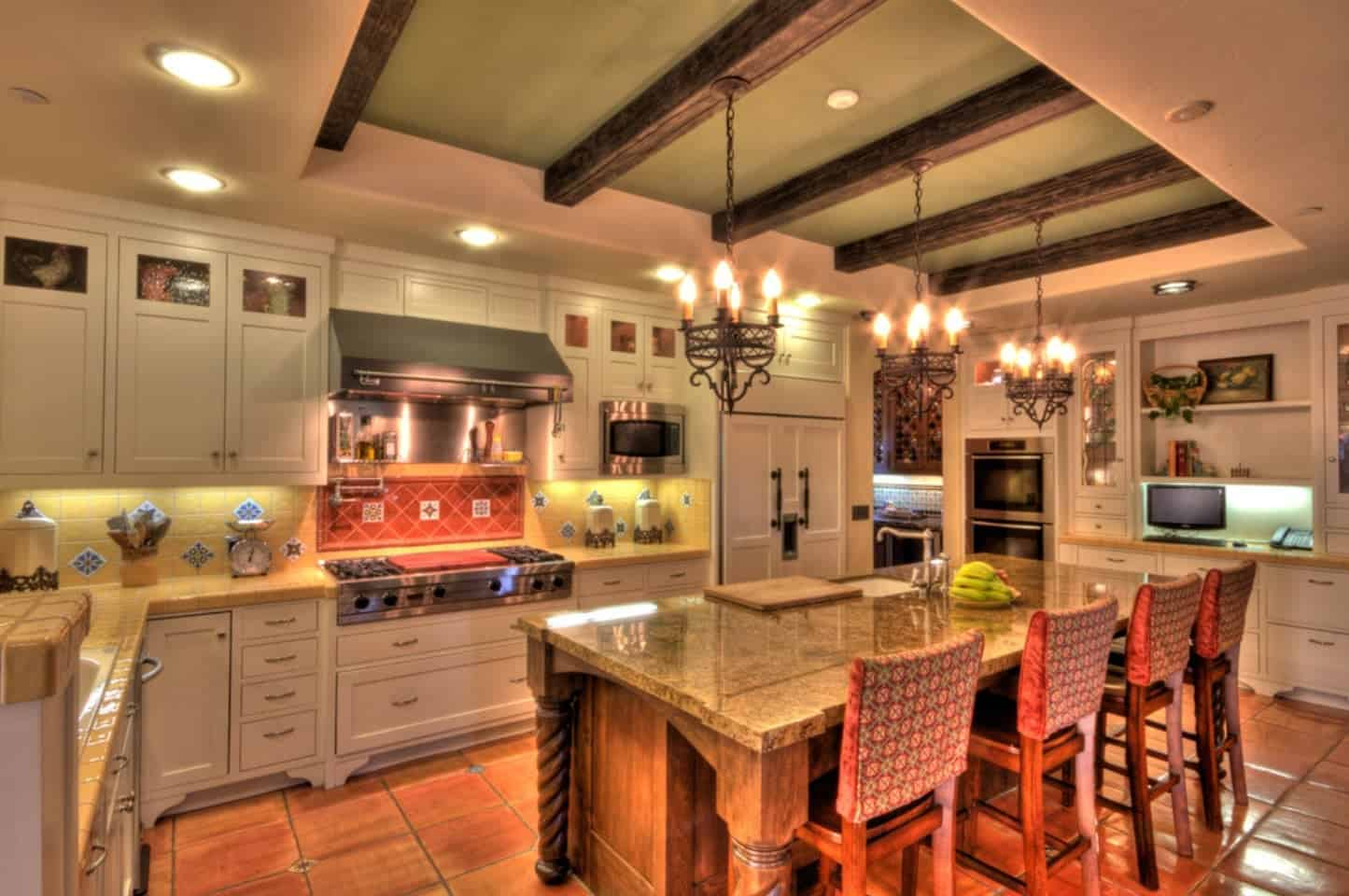 This charming and homey Spanish-style kitchen has a beige ceiling with its middle tray filled with exposed wooden beams. These beams support the small chandelier that cast warm yellow lights on the wooden kitchen island with the same brown marble countertop as the L-shaped light gray peninsula.