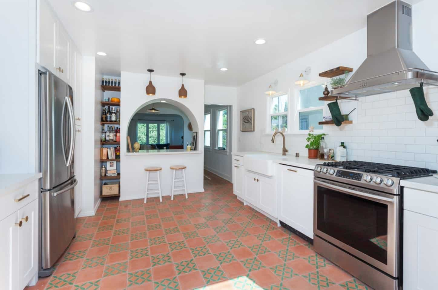 The earthy terracotta flooring tiles have green patterns to it that gives this Spanish-style kitchen a unique flooring that contrasts the bright white cabinetry that houses the stainless steel appliances and the vent hood above stands out against the white ceiling