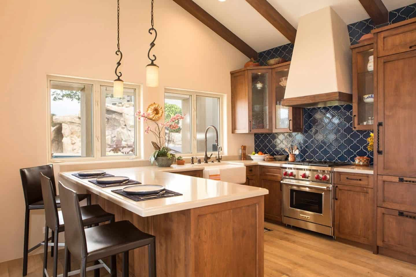 There is a homey warmth and cozy quality to this simple and small kitchen that has a U-shaped wooden peninsula with white countertops. This is topped with a beige shed ceiling with exposed wooden beams that match the cabinetry and the hardwood flooring.