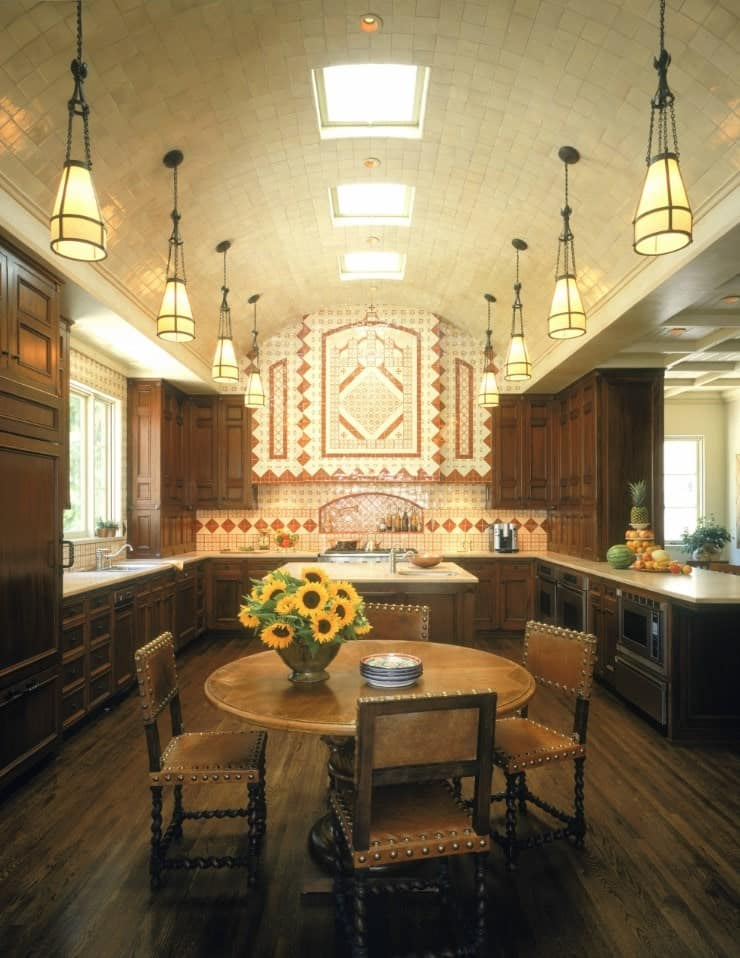 The high cove ceiling of this Spanish-style kitchen has a row of skylights in the middle and two rows of pendant lights over the sides of the U-shaped peninsula that surrounds the kitchen island. These are augmented by an intricate backsplash that extends to the upper wall.