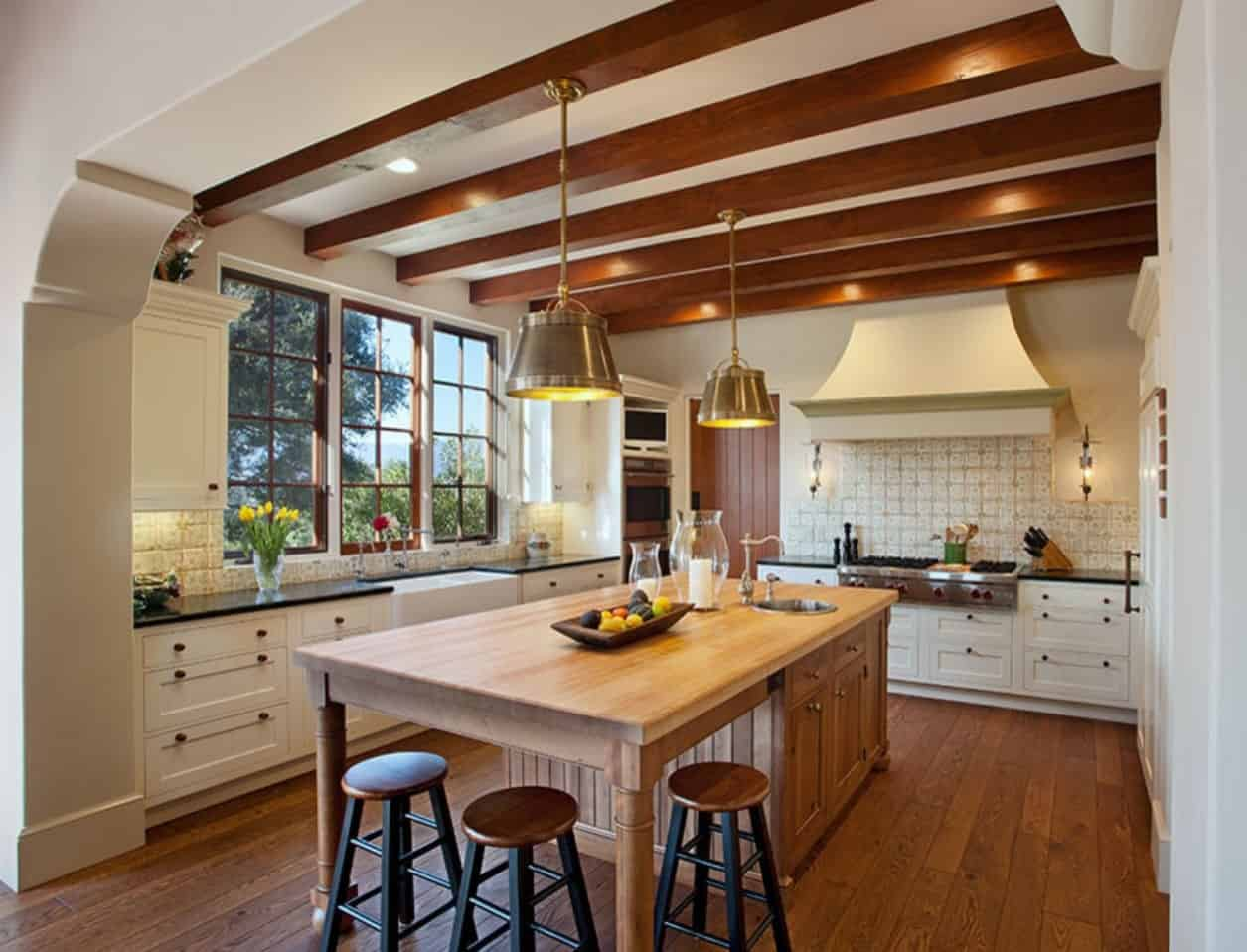 The white ceiling is adorned with exposed wooden beams, recessed lights and a couple of brass dome pendant lights that hang over the wooden kitchen island. This blends with the hardwood flooring and contrasts the shaker cabinets with black handles.