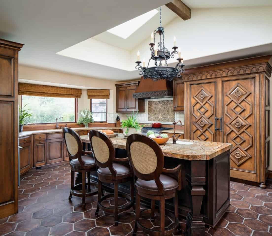 The dark terracotta floor tiles blend with the dark wooden kitchen island that is topped with a wrought iron chandelier and illuminated by the sky light that brings in an abundance of natural lights along with the wide windows of the sink area.