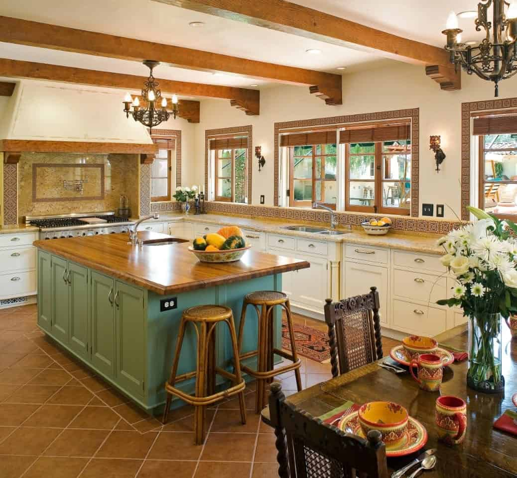 The dark brown iron chandelier hangs from one of the exposed wooden beams of the ceiling. This pairs well with the frames of the windows over the L-shaped kitchen peninsula that is adorned with complex patterned backsplash.