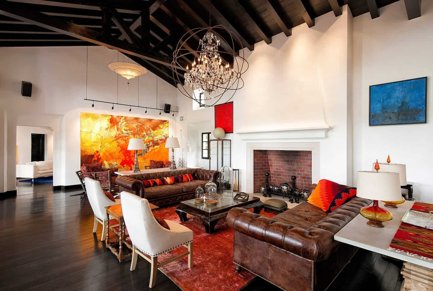 Elegant living room boasts a spectacular chandelier that hung from a wood beam ceiling. It features matching leather sofas and white chairs surrounding a coffee table and the brick fireplace.