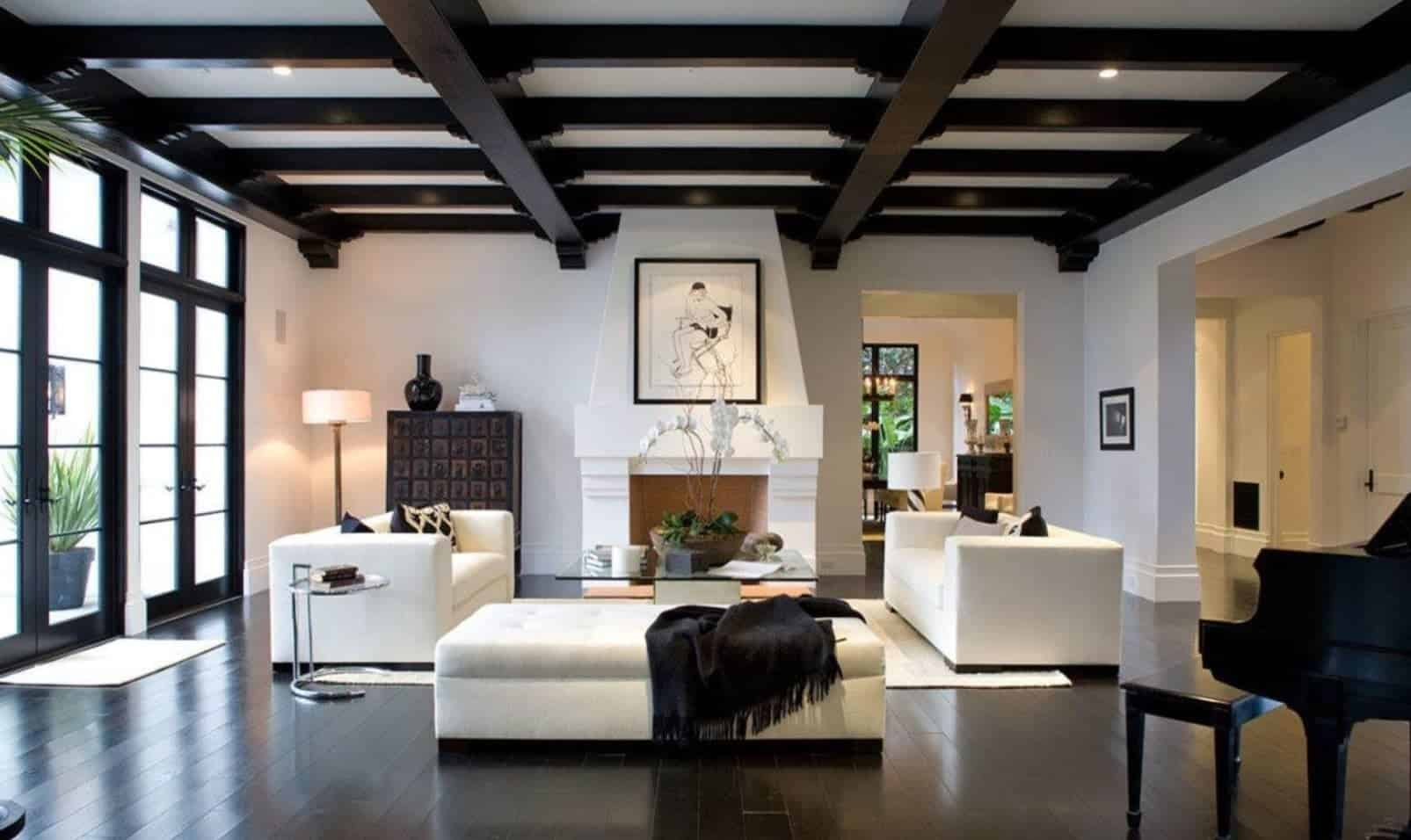 Modern white living room beautifully contrasted with a stylish black beam ceiling and hardwood flooring. It has white matching sofas and tufted bench accented with black pillows and throw blanket.