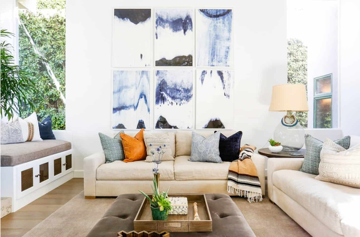 Spanish living room decorated with a multi panel canvas wall art mounted above a beige sectional sofa that's styled with multi-colored pillows and striped blanket.