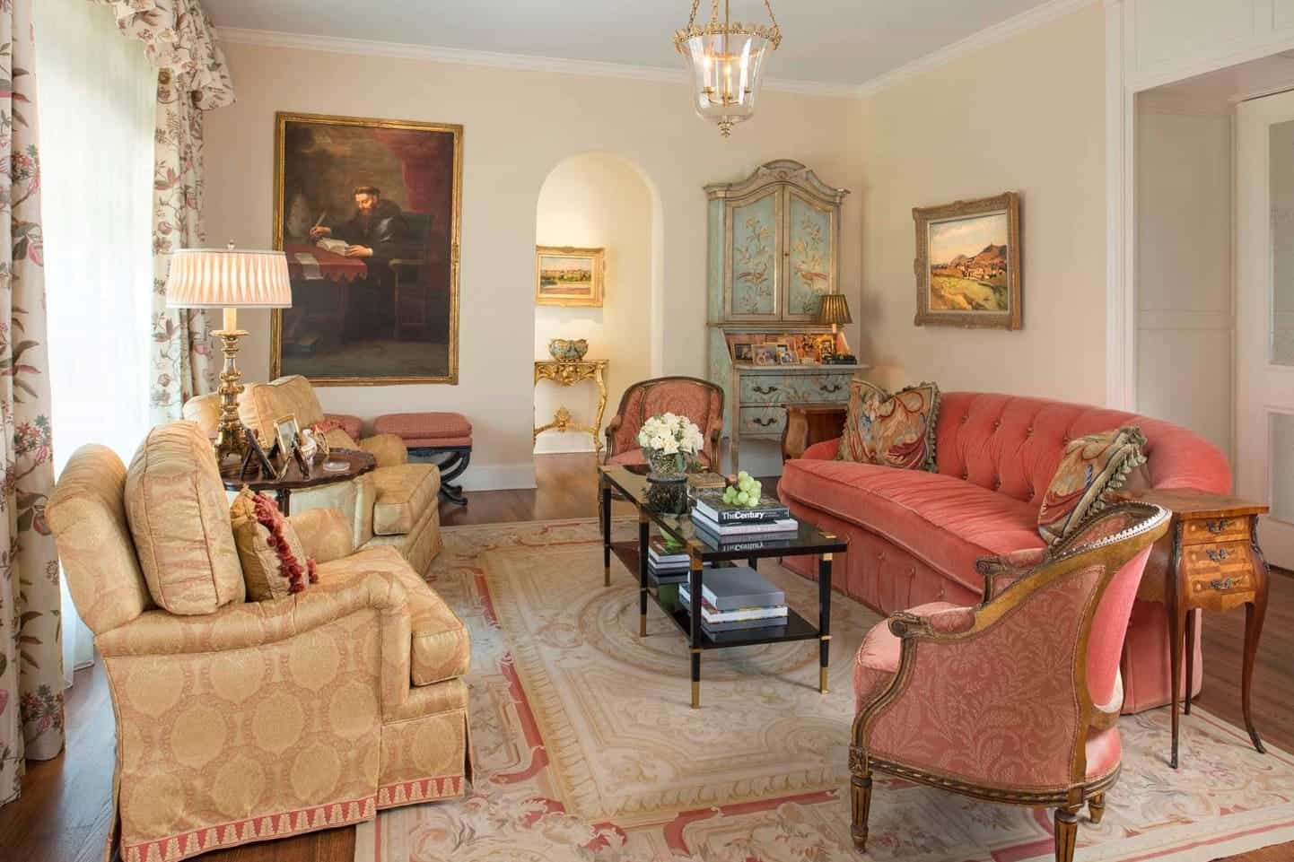 Spanish living room integrated with a Victorian style. It is furnished with a salmon pink tufted sofa and mismatched chairs that centers on a black coffee table over a shabby chic rug.