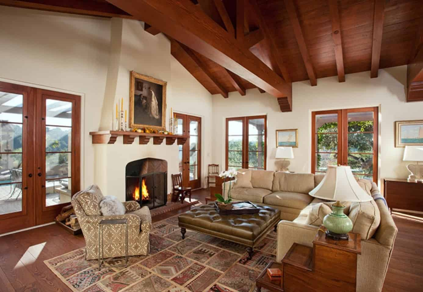 Spanish living room surrounded with glazed doors that complements the wood beam ceiling. It features a fireplace fixed below a lovely painting.