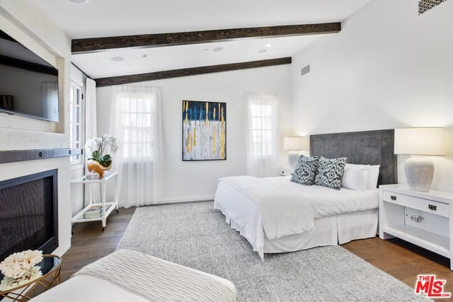 Spanish style bedroom features exposed wooden beams and wooden floors with a gray rug in stark contrast with the white brightness. It also accentuates the colorful wall-mounted abstract painting in the middle of two French windows. In the middle of the room is a white bed with a gray headboard facing the wall-mounted TV above a modern fireplace.