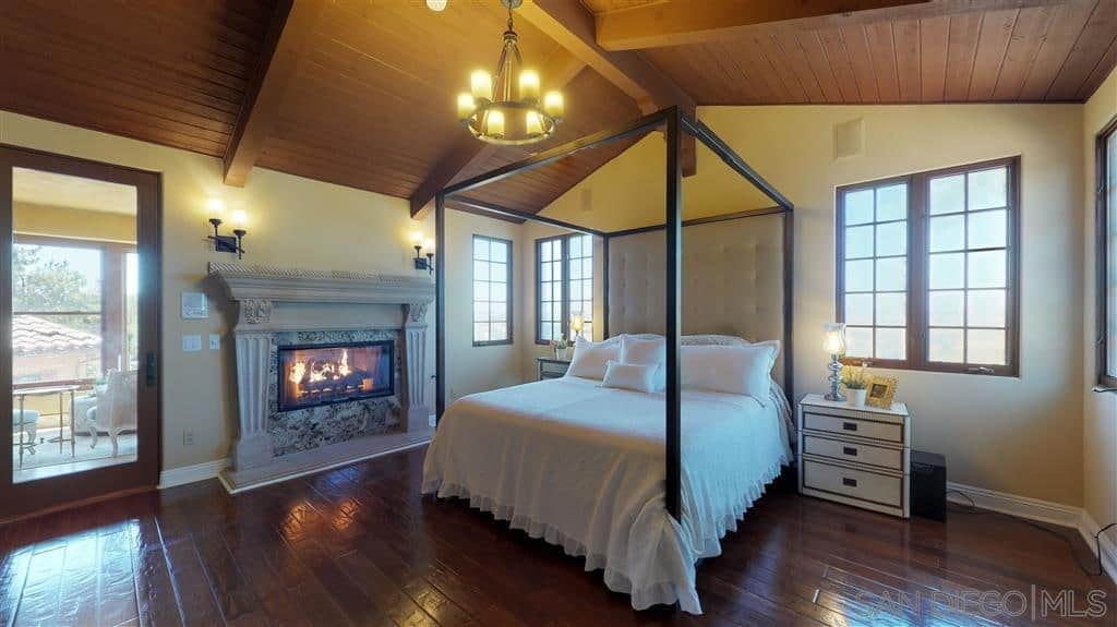 A cozy room that is a combination of Spanish and Cottage style. It highlights the fireplace which is fitted with marble and elegant stone-work beside the wooden four-poster bed. The dark wooden floors are mirrored on the vaulted ceiling and its exposed beams, serving as a background to the stark white linens of the bed and walls.