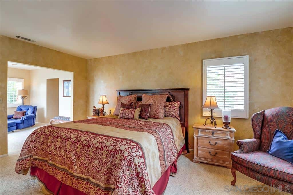 The beige-walled bedroom puts emphasis on the intricate designs of both the bed and French chair beside it. There are distressed side tables on either side of the bed that matches with the beige walls and floor. The Brass lamps are a perfect pairing to the dark brown wooden headboard.