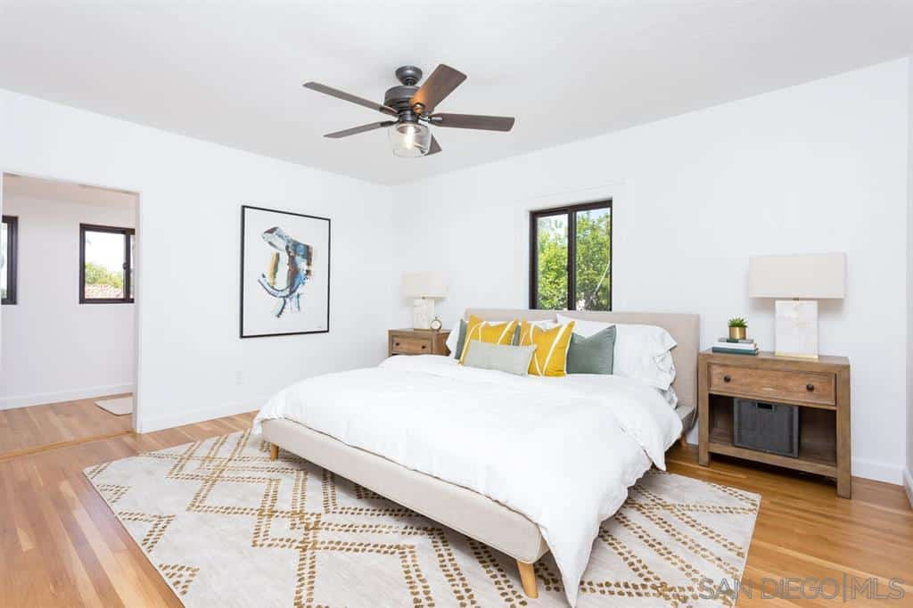 A white and cozy bedroom that features a wall-mounted painting beside a bed with gray headboard. It is flanked by a pair of brown wooden side tables equipped with identical white lamps. The whiteness of the room emphasizes the dark brown ceiling fan with a light fixture.