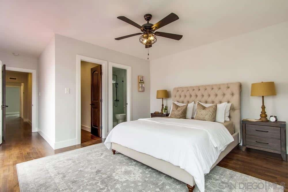 A beautiful faded gray rug dominates the wooden floor that pairs well with the two wooden side tables on either side of the bed. It's beige headboard gives a slight distinction with the white walls and linen of the bed which gives the brass lamp and ceiling fan a good color contrast.