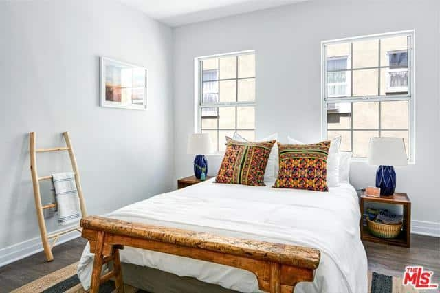 The white room gives off an ethnic vibe with the minute splashes of brown and patterns. The pair of blue patterned lamp vases beside the bed are brilliantly partnered with the simple box side tables. The addition of a wicker basket and ladder towel rack gives a rustic feel to this Spanish bedroom.