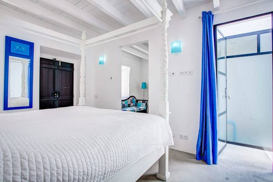 A very bright room with bright white and bright blue colors. The four-poster bed is a good partner to the exposed wooden beams of the ceiling. The added detail of the antique wooden door gives this room a distinctly Spanish character.