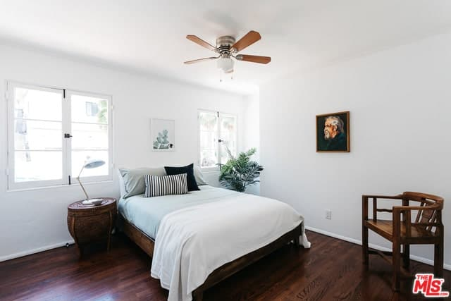 This Spanish style bedroom gives off the illusion that it is divided in half. It is an elegant representation of the sky and earth coming together. The dark brown of the floor, side table, chair and bed frame is at the earthy lower half while the white bed, walls, and ceiling are all sky white.