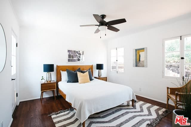 The brilliant addition of the blue and metallic table lamps on either side of the bed is a nice touch of eccentricity to this white and brown Spanish bedroom. It is a nice blend of old and new details like the rattan chair in the corner paired with the modernistic rug in the middle of the floor.