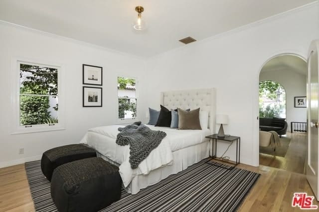 A white bedroom centered with a pin-striped rug with a pair of dark square bean bag chairs. The white bed is paired with a modern side table and a small lamp. The lovely detail of the two wall-mounted framed photos in the middle of the two windows gives this Spanish bedroom a modern minimalistic vibe.