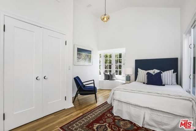 The teardrop lighting paired with the french windows and white walls gives it a modernistic feel. However, the intricately patterned rug brings it back to its Spanish roots. The brilliant addition of navy blue colors into the headboard, chair, and pillow give depth and warmth that balances out the clinical feel of the whiteness.