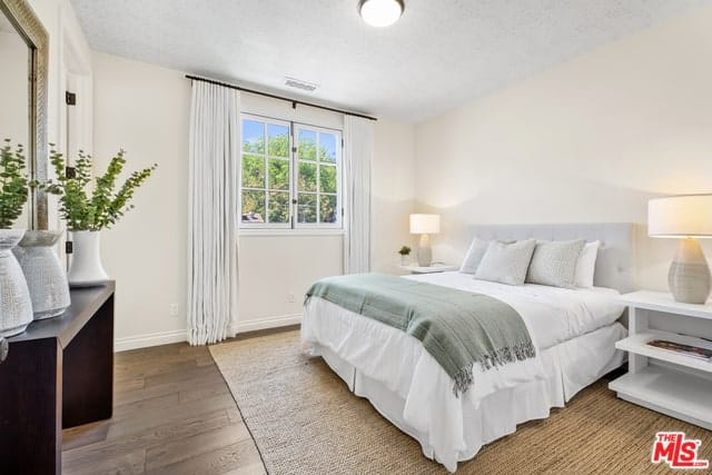 A white Spanish style bedroom with a subtle woven Seagrass rug on a wooden floor. This subtle theme is shared by the flower vases and lamps that appear almost similar. It also shows in the color pairing of the bed, its headboard and whiteness of the walls and ceiling.