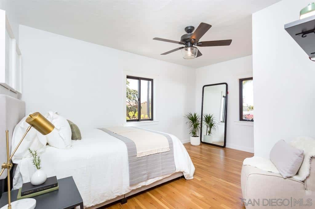 A simple and homey bedroom that is predominantly colored white and gray. This puts emphasis on the wooden brown details of the floor and ceiling-mounted fan with a built-in light fixture. Small details of the green plant and golden brass lamp on the side table add character to the room.