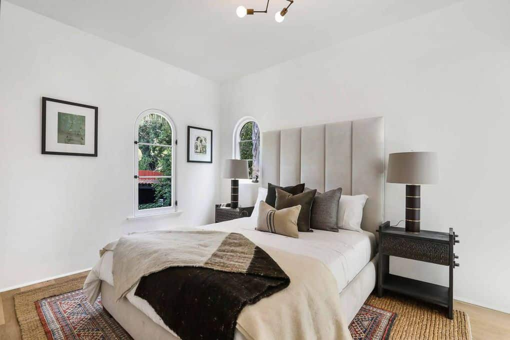 This simple white bedroom is dominated by the woven wicker rug in the middle of the floor. A pair of dark modern lamps sit atop of side tables that goes in contrast with the white walls and light gray headboard. Two arch top windows give accents to the walls along with wall-mounted photos.