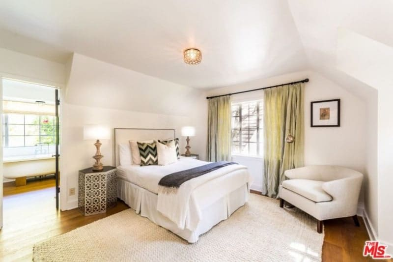 An elegantly simple white bedroom that has a white rug, white bed, white walls and white single sofa chair at the corner. There are brass details that accentuate the room elegantly like the side tables and lamps and the standing lamp by the sofa chair. These are all illuminated by a ceiling-mounted flush lighting with an intricate brass design.