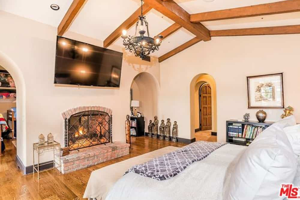 The bricked fireplace offers this Spanish bedroom a warm cozy vibe that is further enhanced by a dark iron chandelier hanging from an arched ceiling with exposed wooden beams. The cottage style elements blended with the Spanish perfectly and are peppered with eccentric details like small brass statues and figurines.