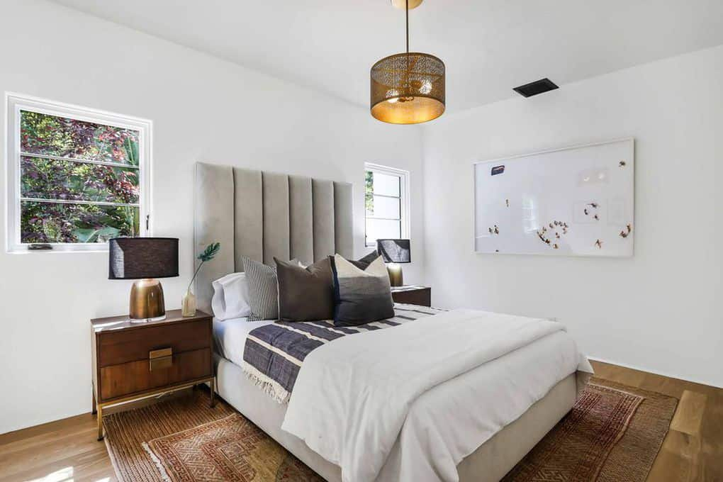 This bright white Spanish bedroom features a golden teardrop lighting on top of a white bed with a gray headboard. A pair of brass table lamps are situated by the two square windows. The warm accent to the room is the woven patterned area rug in the middle room.