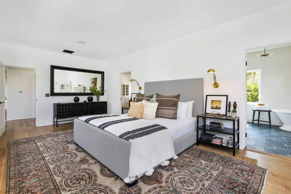 The spacious primary bedroom has a pair of small golden wall-mounted lamps on either side of the pin-striped headboard. It is flanked by three-tiered shelves that mirror the color and tone of the console table besides the bed. This is below a massive rectangular wall-mounted mirror. All the details are brought together by a large patterned rug in the middle of the room.