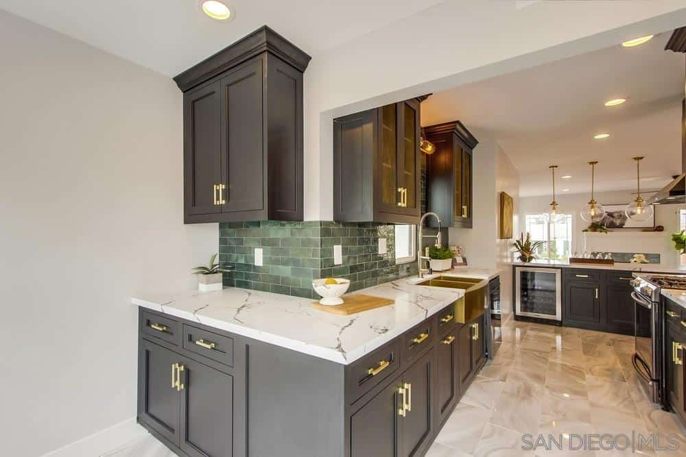 The gray shaker cabinets and drawers of the peninsulas follow the lay of the white walls that is complemented by the gray tiles of the backsplash arranged in a brick wall pattern. The golden sink and the golden <a class=