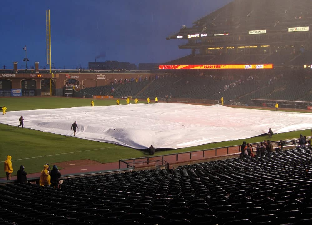Crew covering infield with tarp as it starts to rain during a game.