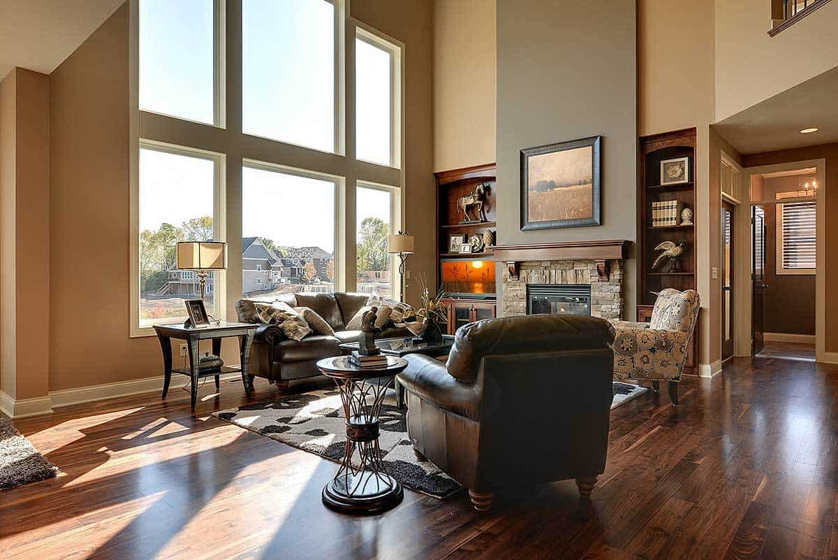 The tall glass wall of this living room gives a balance to the dark brown leather sofa and armchair that matches well with the dark hardwood flooring and the two embedded wooden shelves flanking the stone fireplace.