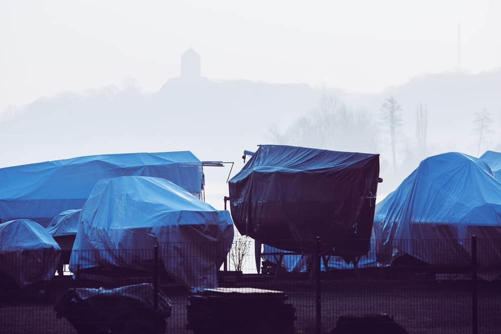 Boats of different sizes covered in blue tarp.
