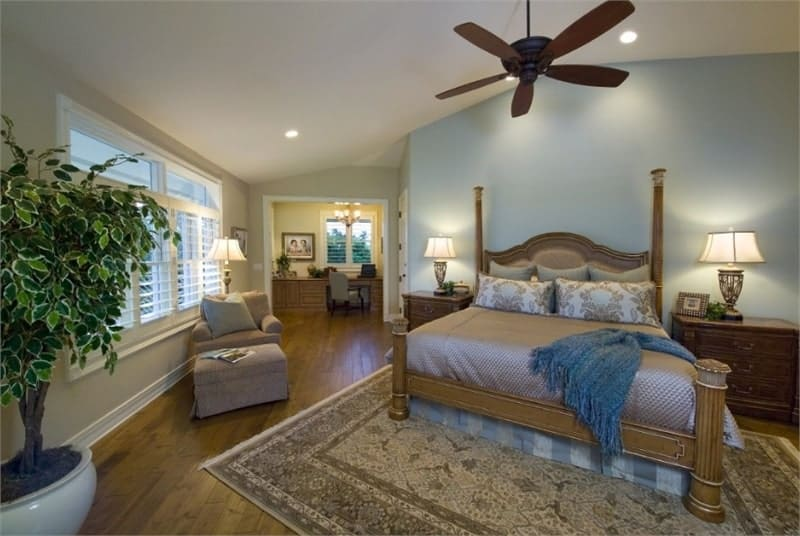 The primary bedroom has a large wooden four-poster bed paired with wooden bedside drawers, a large patterned area rug and a dark brown ceiling fan that stands out against the beige ceiling.